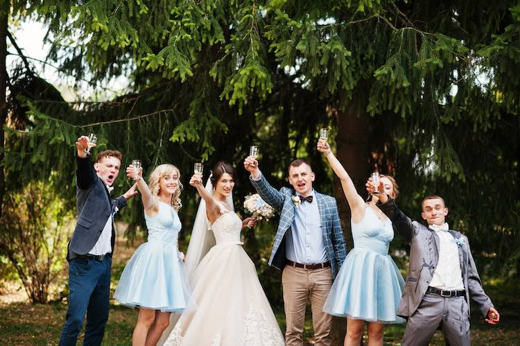Stunning wedding couple with bridesmaids and groomsmen drinking champagne in the park on a perfect sunny day.