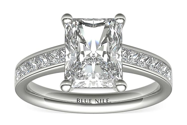 Diamond engagement ring showcasing twelve princess-cut diamonds channel-set in 14k white gold and accenting a center diamond. (Photo by Blue Nile).