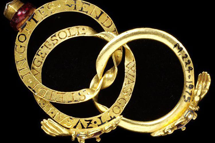 "A gimmel ring made of three interlocking hoops. When worn, the diamond-set heart at the front of the ring is encircled by a pair of clasped hands. Germany, circa 1600-1650. Designed in gold, enamel, and set with a diamond. The second quotation from the marriage service indicates that the ring was used as a marriage ring in Germany. The entire rings says ""My beginning and my end' and 'What God has joined together let no man put asunder."" (Photo courtesy of the Victoria and Albert Museum)"