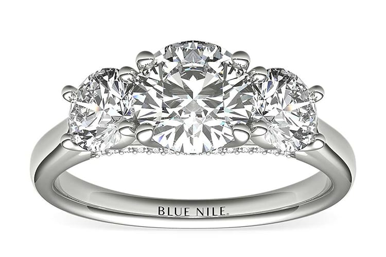 Three-stone ring with pavé-set diamond detailing all set in enduring platinum. Photo courtesy of Blue Nile.
