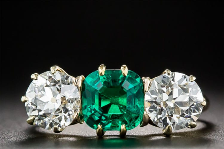 Lang Antiques 1.30-carat Colombian emerald flanked by a pair of bright white European-cut diamonds, weighing 1.00 and 1.10 carats, respectively. The three stones are featured in a hand-fabricated 14K yellow gold early-twentieth century ring