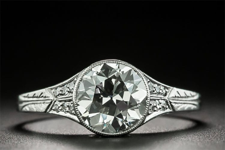 Lang Antiques Late Edwardian 1.82 carat old European Cut platinum ring accented with diamonds and hand engraving.