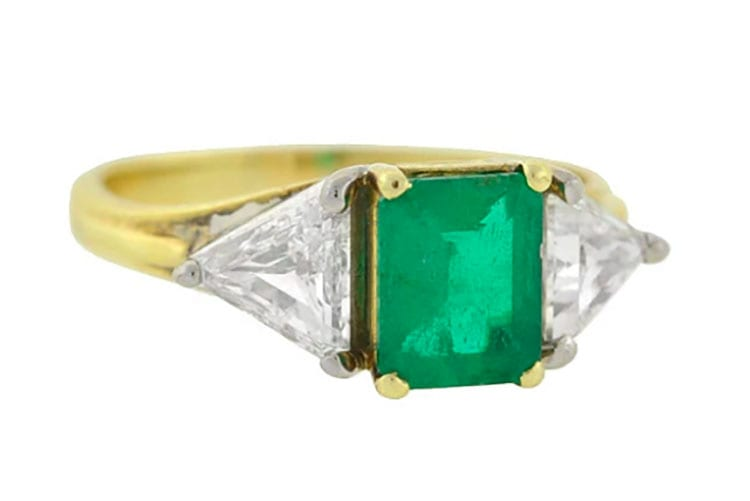 A. Brandt & Sons vintage 18K gold emerald and diamond ring, circa 1960s. The emerald is approximately .90-carats in emerald cut, flanked by two diamond trillion cuts on the sides.