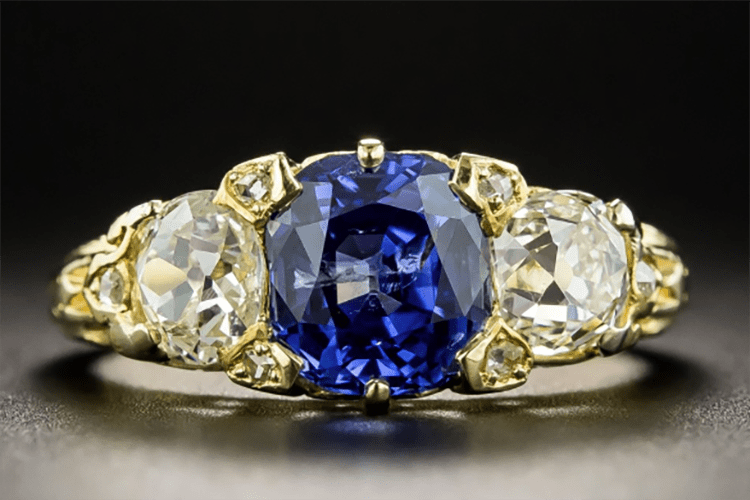Lang Antiques 18K yellow gold three stone Victorian ring set with 2.41royal blue cushion-cut sapphire, between a pair of old mine-cut diamonds,