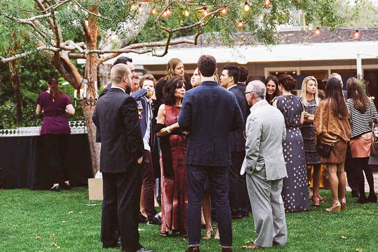 Wedding guests mingle outside during cocktail hour