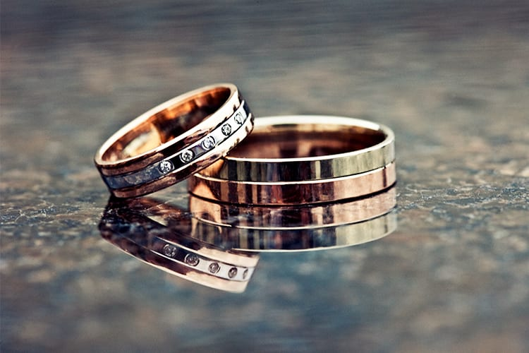 Metal wedding bands on a shiny surface