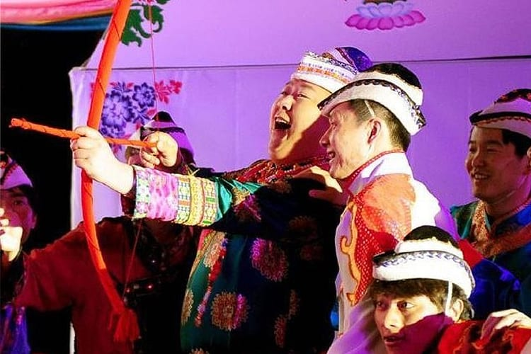 As part of a Chinese wedding tradition, the groom shoots arrows at the bride