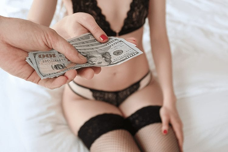 A woman in lingerie sitting on a bed accepts money