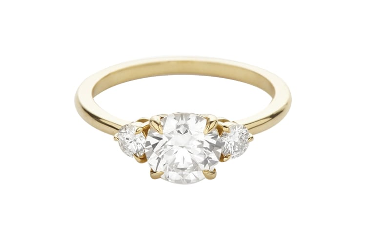 A sleek yellow gold band set with three round stones is one of the most  classic engagement ring settings. Your love might not be textbook but like  this ring ... 741bb1dfa3