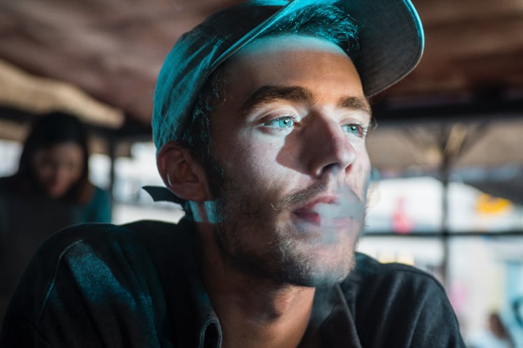 Man in cap smoking, looking kind of stoned