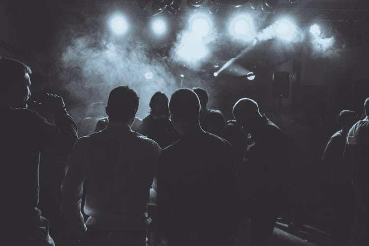 A group of men smoke on a dance floor