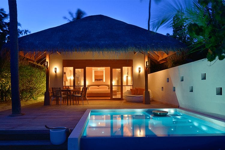 Maldives Honeymoon - View of thatched roof villa and pool at night