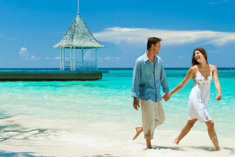A couple walks along the beach at Sandals Royal Plantation Resort in Ocho Rios, Jamaica
