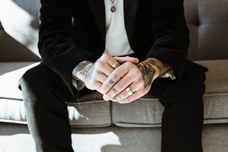 Man sitting on a couch with several different types of wedding bands