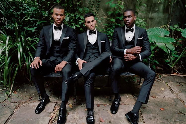 Three men in tuxedos on a bench