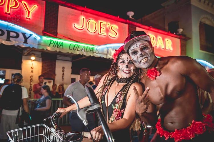 Couple on bikes posing outside Sloppy Joe's Bar