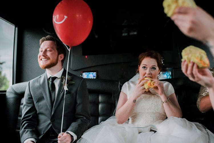 A bride has a taco in the back of the limo with her groom