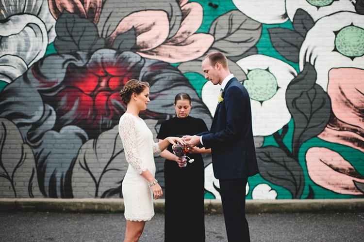 A couple is married in front of a mural of flowers
