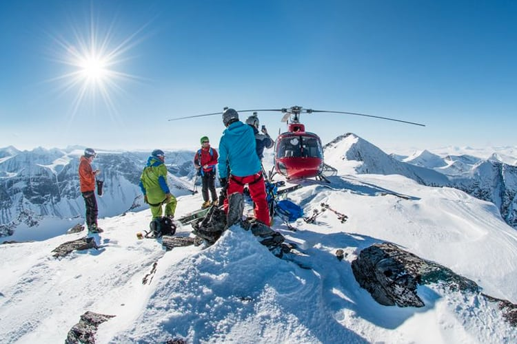 Extreme Sports Bachelor Party - Skiers on top of a ridge with a helicopter
