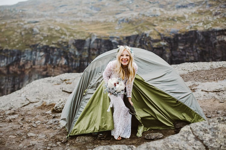 A bride emerges from a tent in her wedding dress
