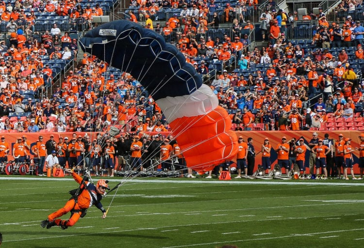 A parachutist lands on the field at Mile High Stadium in Colorado