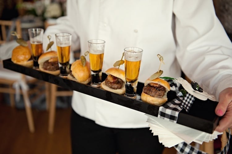 Mini cheeseburger sliders presented on tray with mini beers