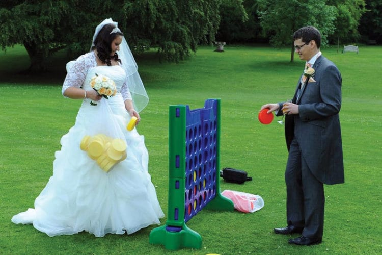 A newlywed couple plays an oversize version of Connect Four