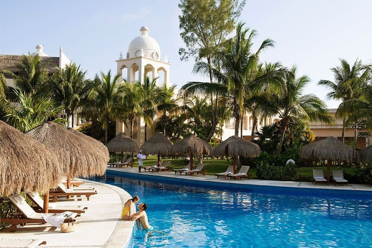 Mexico Honeymoon Guide - woman sitting on side of pool talking to husband who is in the pool