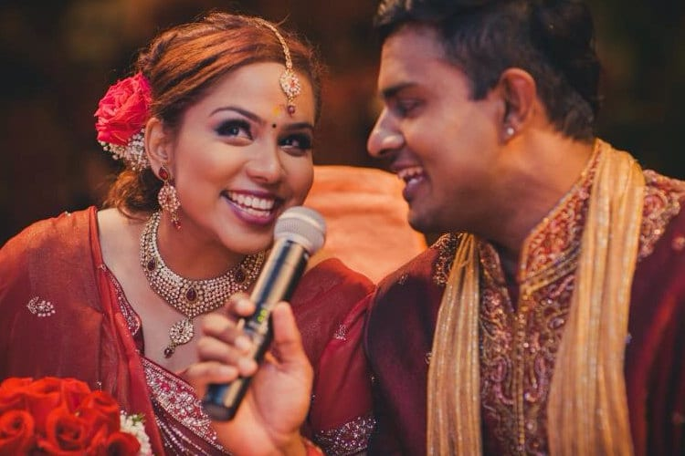 A bride and groom at an Indian wedding share a microphone