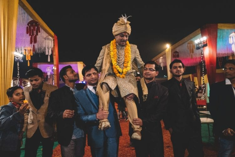 An indian groom is carried into the ceremony by his groomsmen.