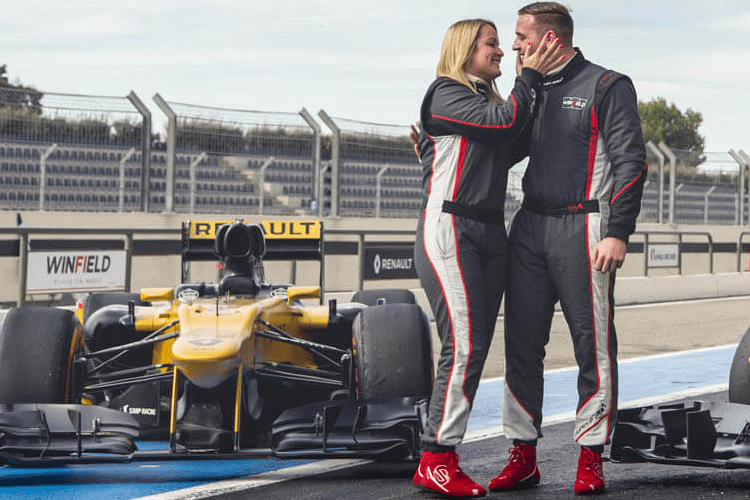 A couple in racing outfits next to a Formula 1 car