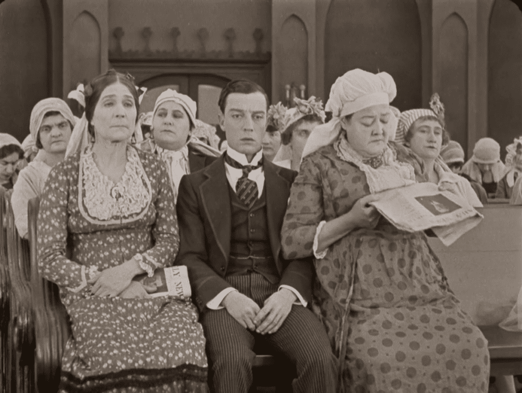 Buster Keaton sitting in a church with a crowd of women hoping to marry him, from the film Seven Chances.