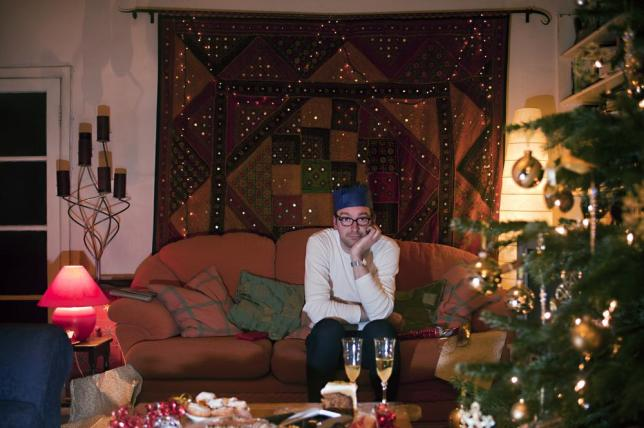 A man sits alone in his living room on Christmas eve