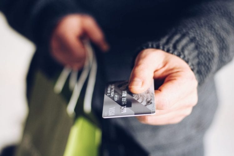 A man extends a credit card to pay for some gifts