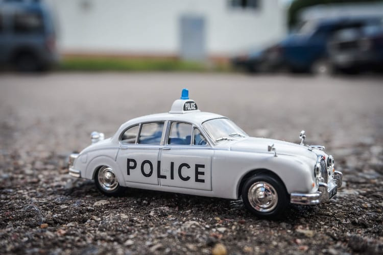 A tiny toy police car on a gravel driveway