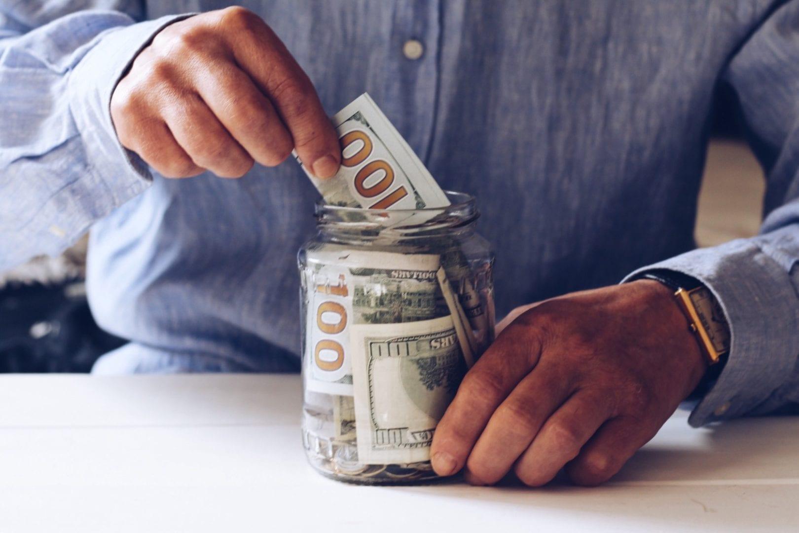 A man puts $100 bills into a jar for savings