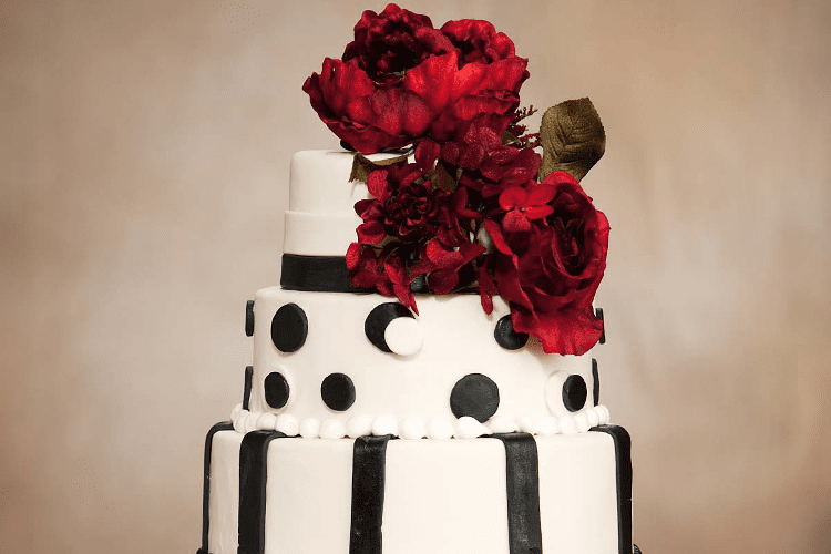 A wedding cake with red roses on its top