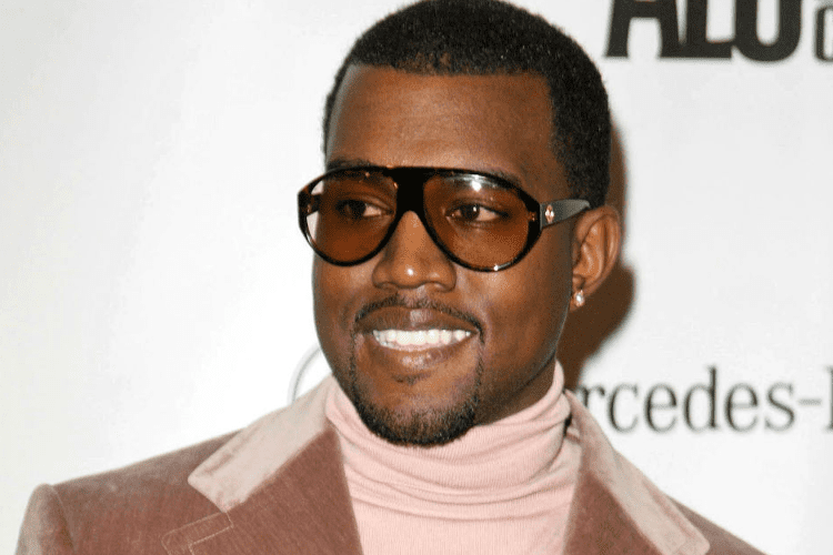 Kanye West wearing sun glasses and smiling