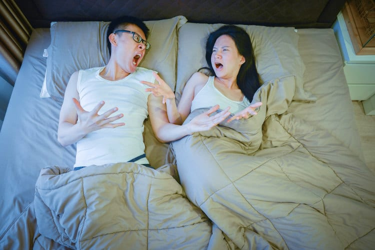 A couple arguing in bed