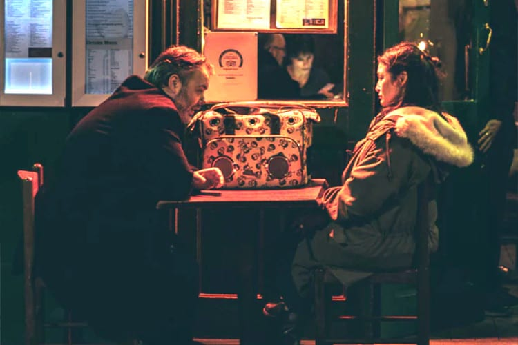 A couple have a serious conversation at a cafe.
