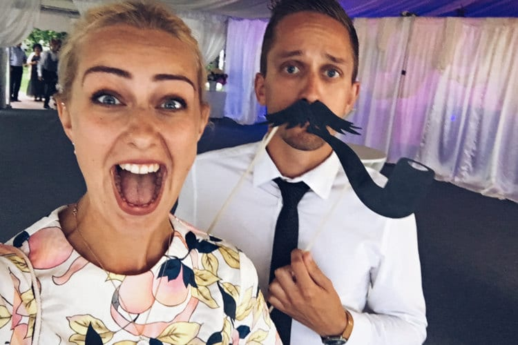 A couple clown around at a wedding