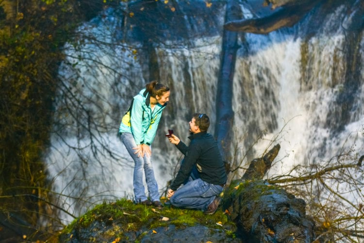 A man proposes to a woman in front of a waterfall