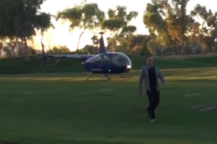 Man walks across a golf course green, a helicopter behind him.